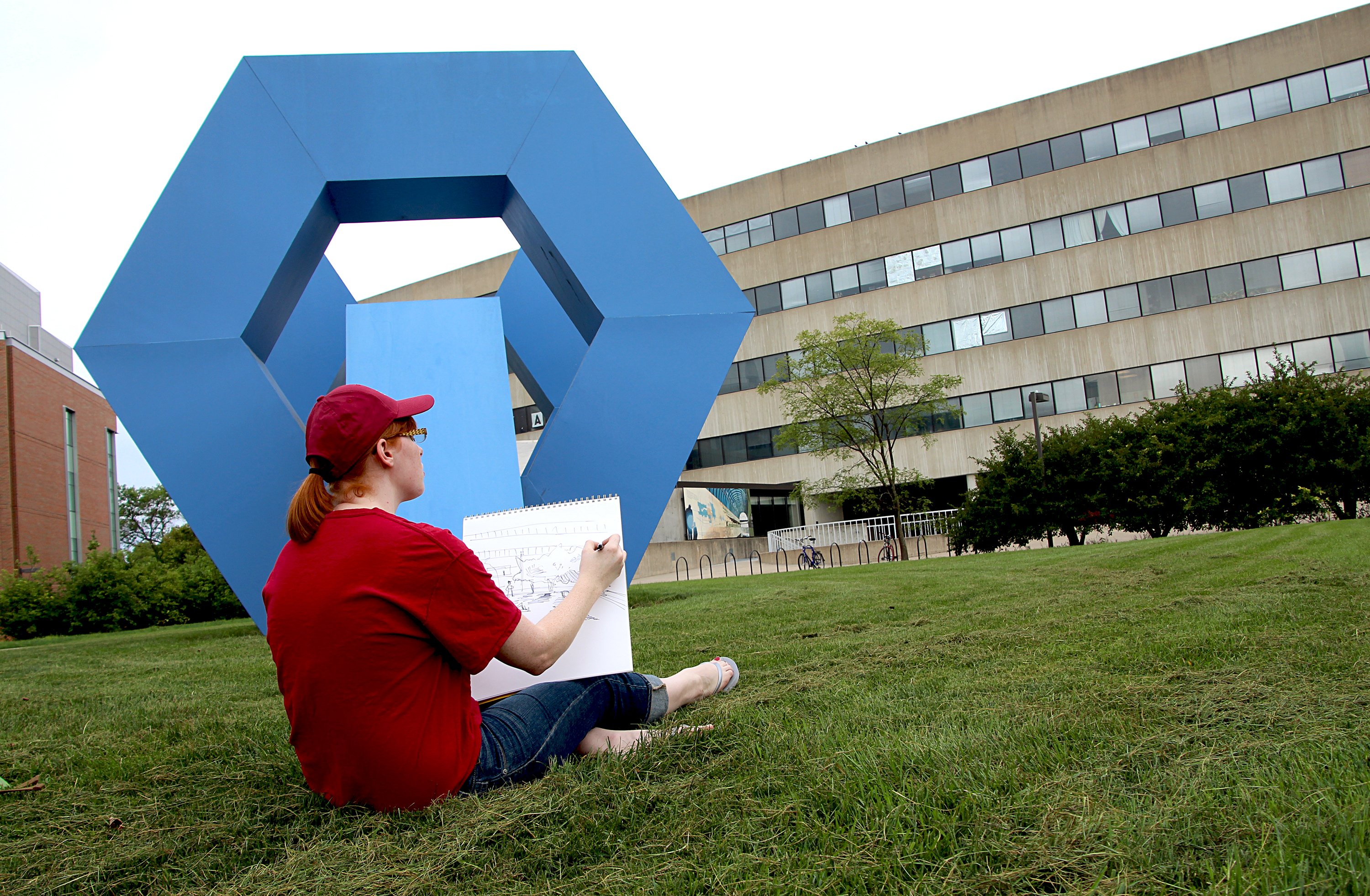 Integrated visual arts graduate student Taylor Carlson sketches the College of Design building.