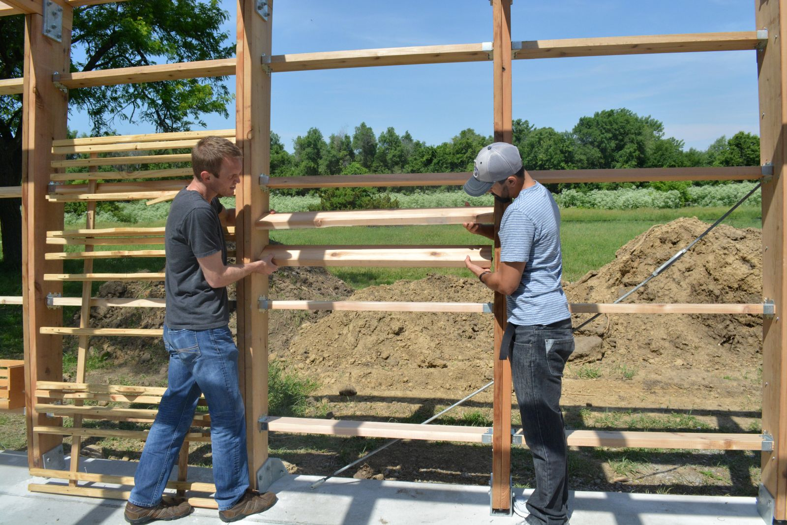 Mark Moeckl, left, and Noel Gonzalez test a full-scale mockup of the louvers on site at the park in Urbandale to see how much sun is blocked.