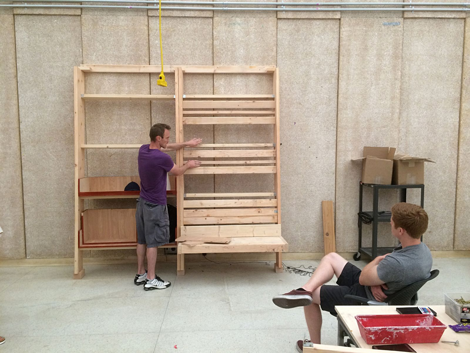 Architecture graduate students Mark Moeckl, standing, and Shawn Barron use a full-scale mockup built at Iowa State to evaluate the spacing of the bench backrests, shelving and louvers.