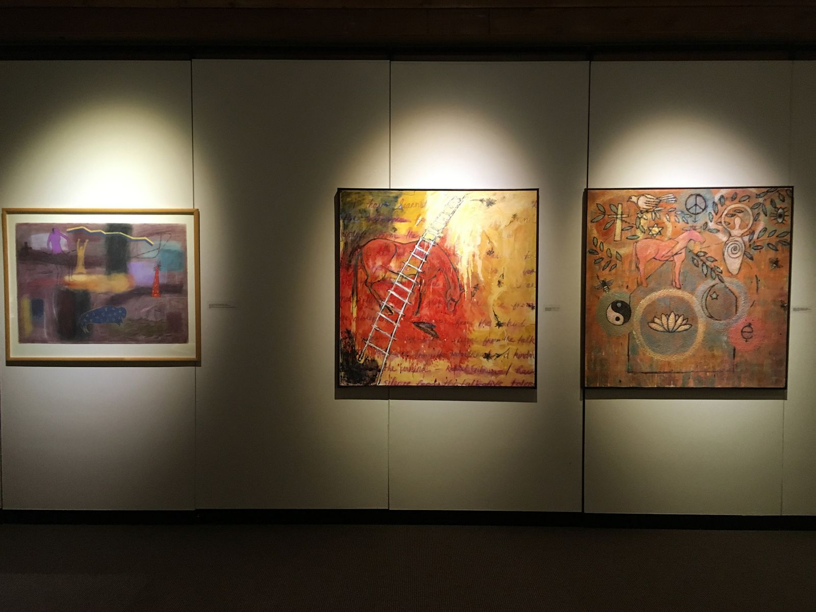"""Red Rise,"" 2016 (microcrystalline wax and oil paint on canvas), center, and ""Maneuvers of the Modern Dance,"" 2016 (beeswax and pigment on baltic birch panel), right, both by Art and Visual Culture Associate Professor Barbara Walton, were inspired by ""Ghost Dancer,"" 1981 (pastel on paper), by Jaune Quick-to-See Smith."