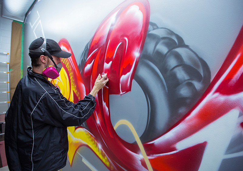 Alumnus Tim Westrom (BFA 2017 Integrated Studio Arts) wears a respirator while he works on a mural for recreation services in a Beyer Hall fitness room. Photo by Christopher Gannon.