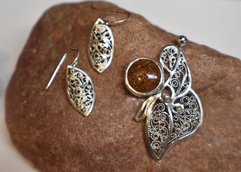"""Where the Dinosaurs Roam"" (dinosaur bone agate, sterling silver), 2.75"" x 1.5"" pendant and 0.5"" earrings, by Lauren Haylock"