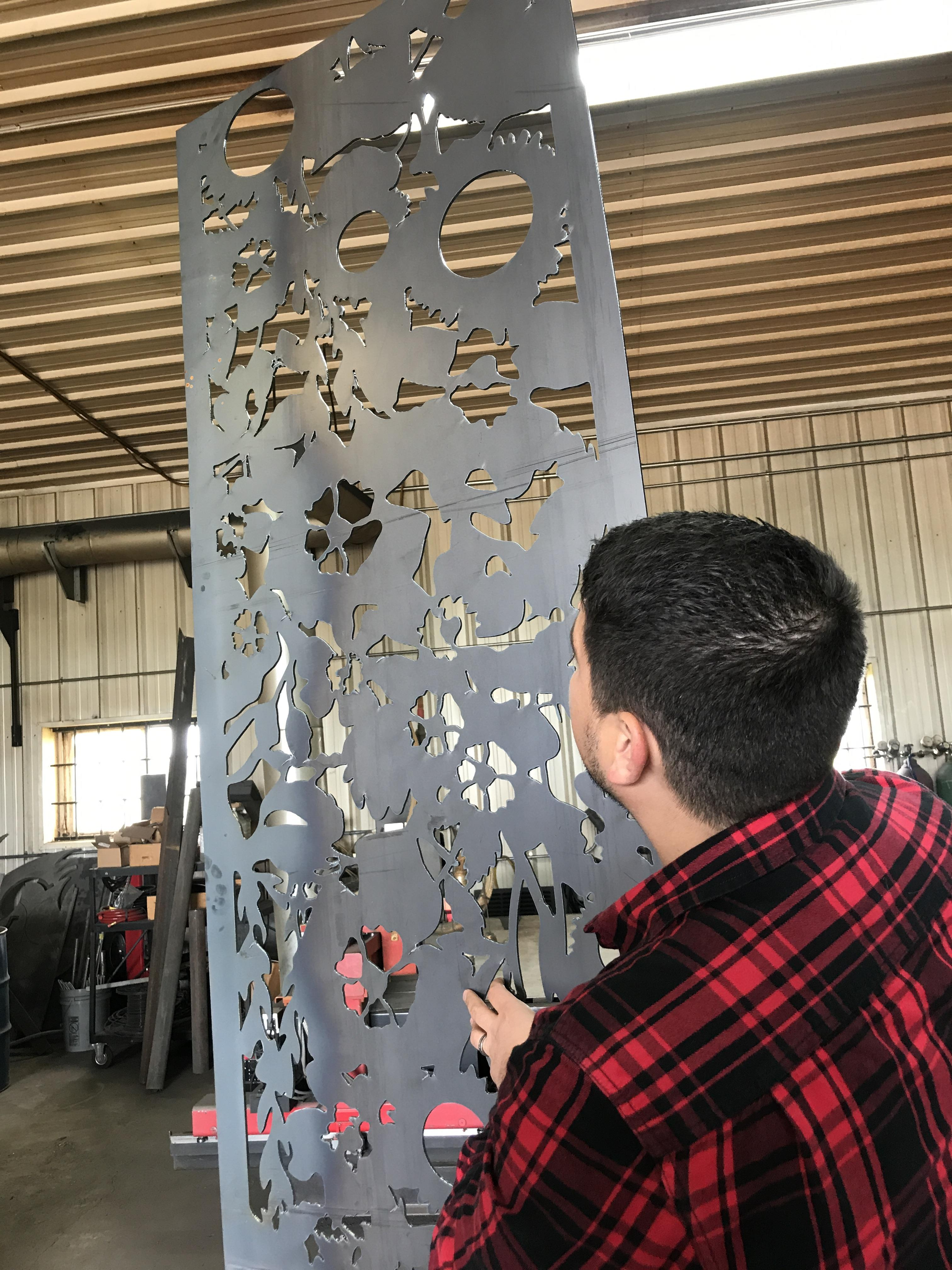 "ISU architecture lecturer and artist Reinaldo Correa with one of the plasma-cut steel panels he designed for the ""Prairie Revival"" sculpture for Lowe Park, Marion, Iowa"
