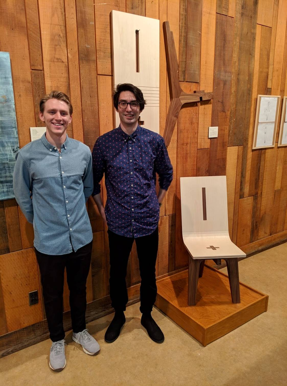 Nathan Miklo and Samuel Christianson, seniors in industrial design, with the flat-pack chair they designed for a Focus Grant project. The project is a finalist in the AWFS Fresh Wood student furniture design competition.