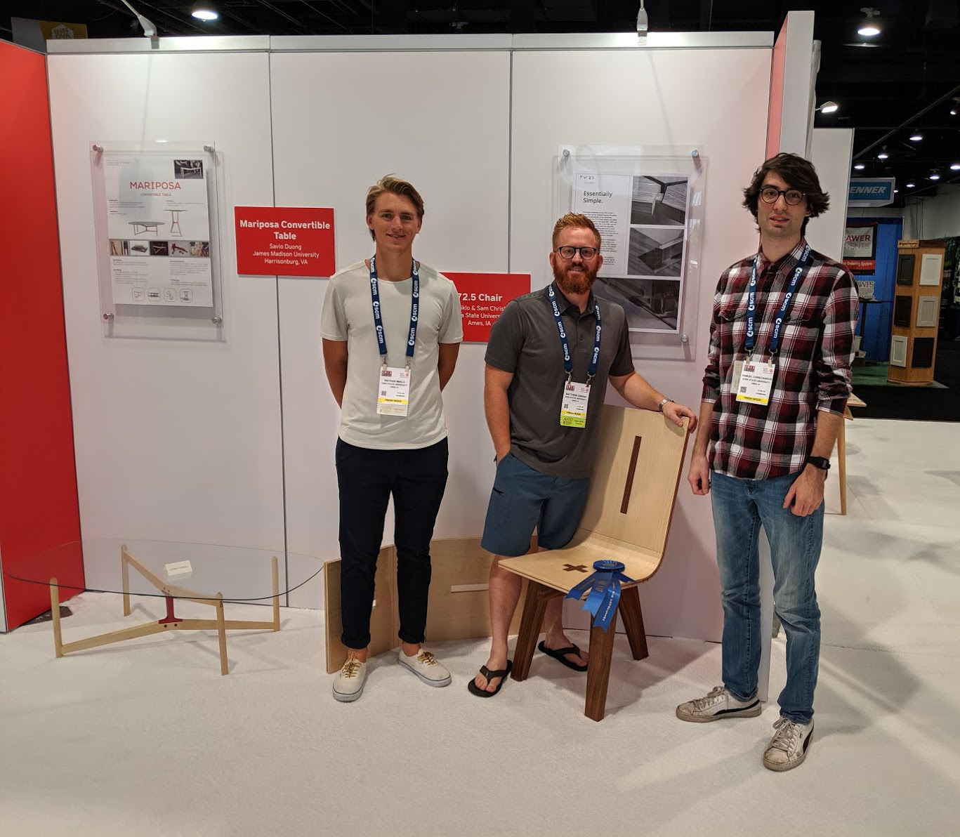Iowa State industrial design students Nathan Miklo, left, and Sam Christianson, right, with instructor Matthew Obbink and their award-winning 72.5 Chair at the 2019 AWFS Fair in Las Vegas