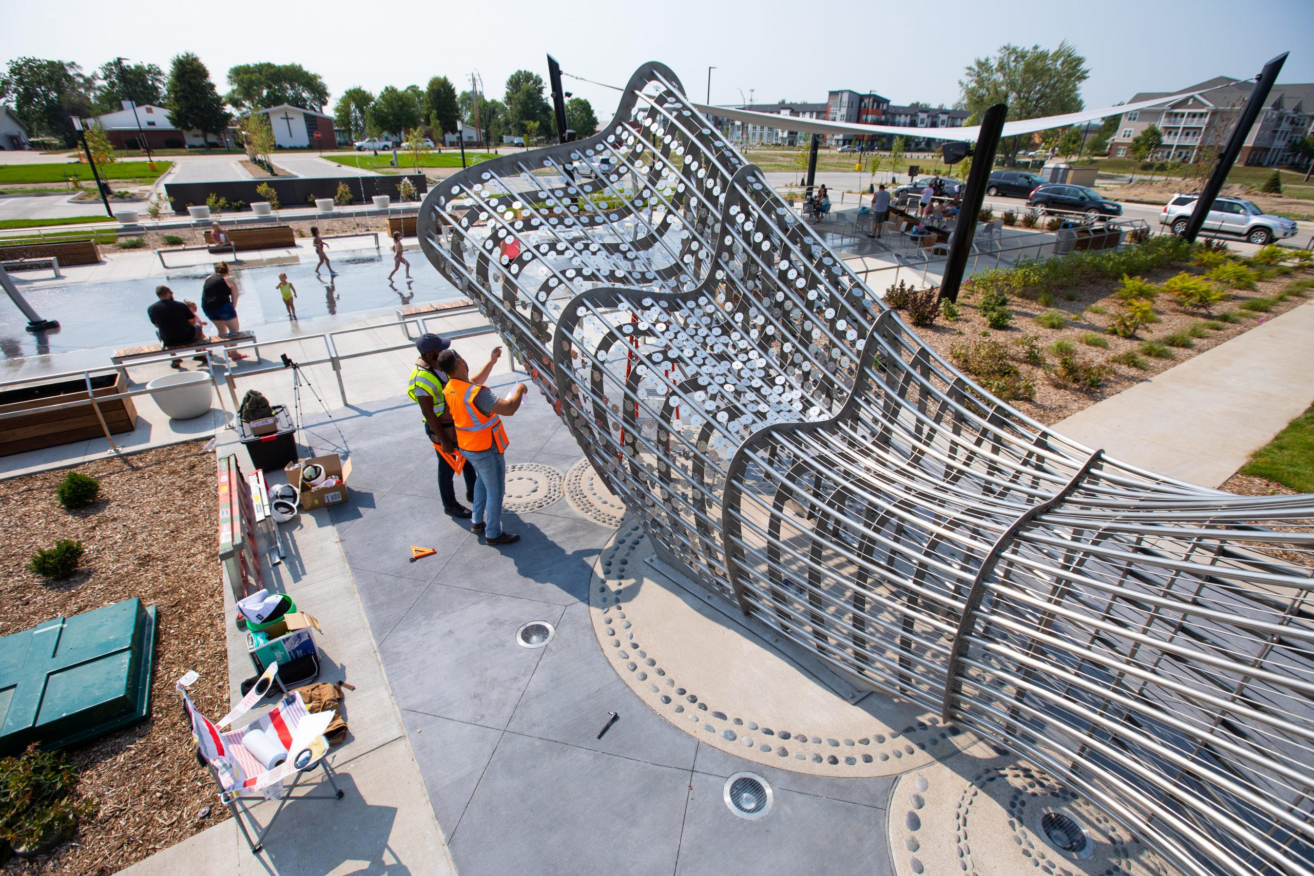 """Installation of kinetic scales on the College of Design art installation, """"Ripples"""" at the Johnston Town Center on July 27, 2021. Reinaldo Correa-Diaz and Ayo Iyanalu work together on the kinetic scales installation. (Christopher Gannon/Iowa State University)"""